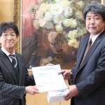 小林清木校長に記念ボールや飲料を手渡した玉北部毎日会の小川智会長